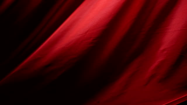 the chic and elegant texture of the moving folds of light red fabric on a black background under dramatic lighting. slow motion 200 fps - тюль ткань стоковые видео и кадры b-roll