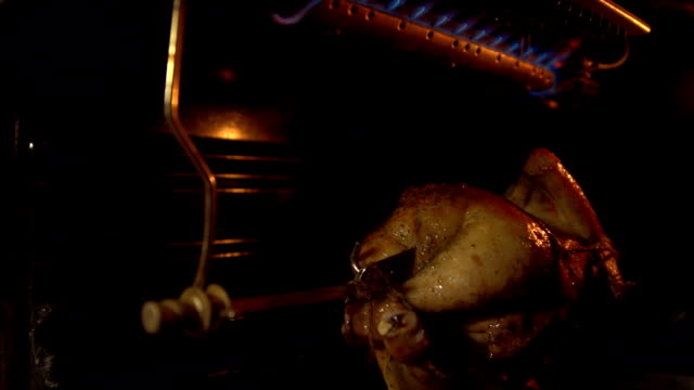 The chicken in the oven roasting on a spit. video