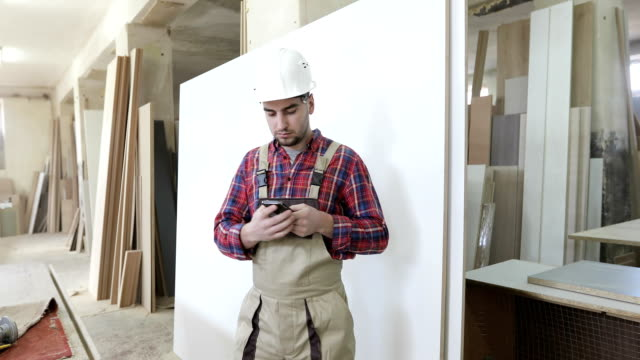 4K The chief carpenter in the joinery uniform and a white helmet answers the phone call. video