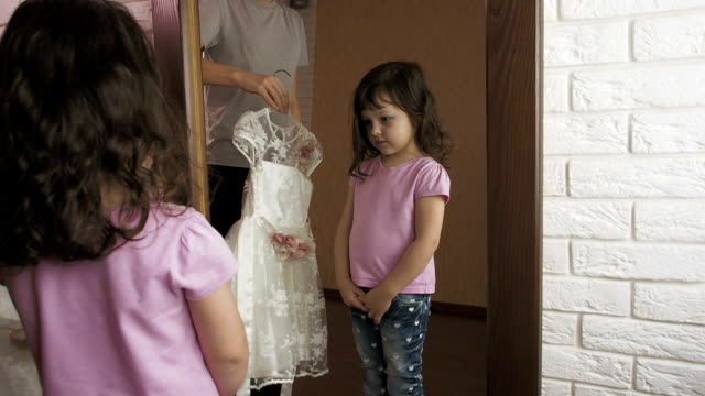 The child at the mirror. The child at the mirror. The woman gives the little girl a beautiful dress. charming stock videos & royalty-free footage