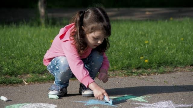 das kind stützt sich auf den asphalt. - kreide weiss stock-videos und b-roll-filmmaterial