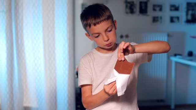 the child eats a chocolate bar, breaks off a piece with his hand - banchi scuola video stock e b–roll