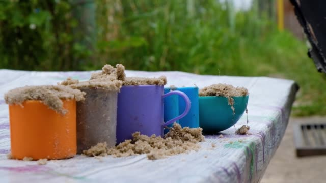 the child folds small forms, mugs with sand