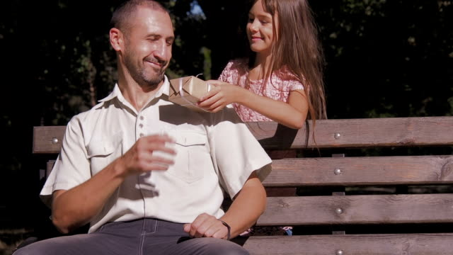 The child gives a gift to the father. video