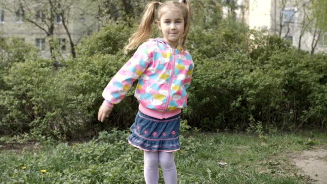 il bambino sta attivamente giocando e muovendosi. la piccola studentessa balla all'aperto e gioisce. felice bambina di 7 anni che balla la danza del filo interdentale si muove all'aperto sulla strada suburbana. rallentatore, uhd 4k. - braccio umano video stock e b–roll