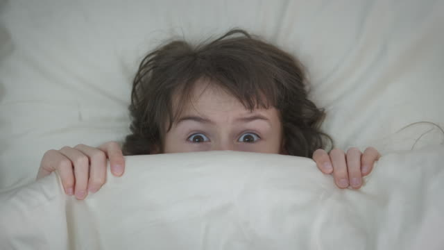 The child is afraid under the covers.