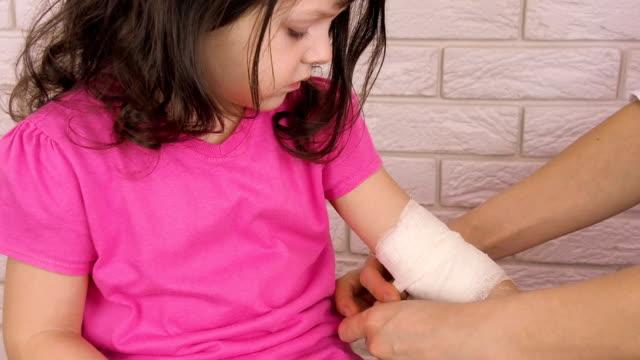 çocuğun elinden tutup sargılı - gazlı bez stok videoları ve detay görüntü çekimi