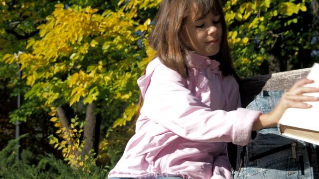 çocuk parkta okuyor. - dijital yerli stok videoları ve detay görüntü çekimi