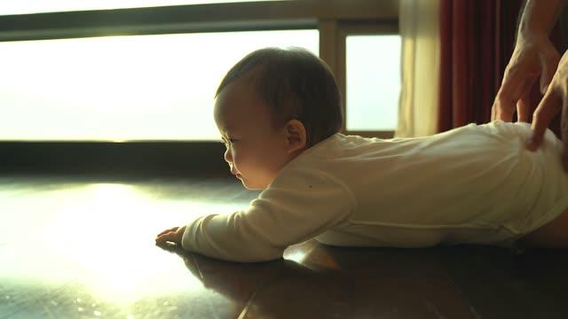 子供をクロールしようとしています。キュートで愛らしい新生児は、クロールと次の世話をする父をみてください。 - 希望点の映像素材/bロール
