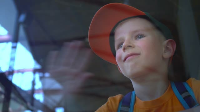 the child looks through the glass at the airport, smiles and waves, the boy meets, sees off someone at the airport - sventolare la mano video stock e b–roll