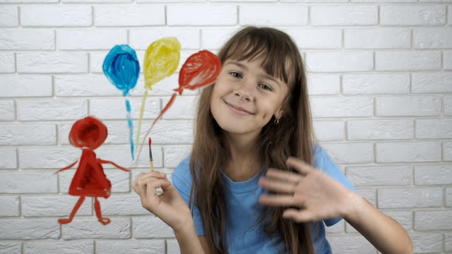 The child paints The child paints. Little girl draws on the glass. charming stock videos & royalty-free footage