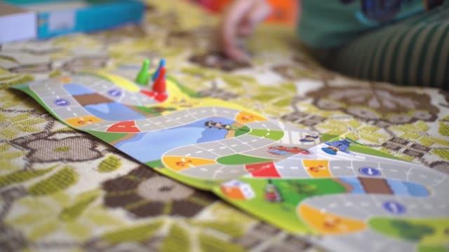 vídeos y material grabado en eventos de stock de el niño juega un juego de mesa con un cubo, en el juego van con fichas y las mueven. - tablón