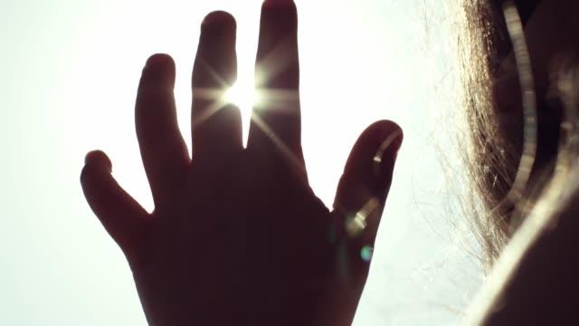 dziecko bawi się promieniami słonecznymi. natura. sylwetka dziecka. - podświetlony filmów i materiałów b-roll