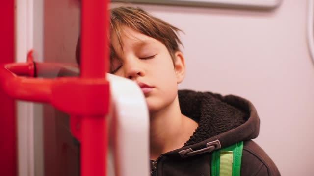 vidéos et rushes de l'enfant monte dans le train, s'endort, dort, se réveille - wagon