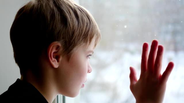 barnet sitter på fönsterbrädan- och tittar ut genom fönstret på snön närbild - snow kids bildbanksvideor och videomaterial från bakom kulisserna