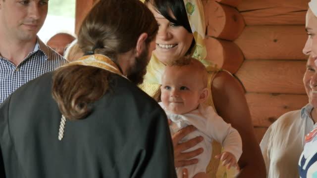 子供の洗礼の儀式の時に司祭に笑顔します。 - 洗礼点の映像素材/bロール