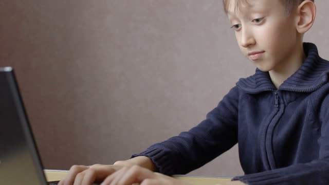 the child works on laptop online video