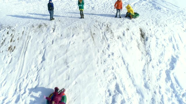 The children are playing and rolling down a hill on snow inflatable sled video