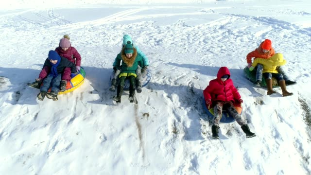 The children are playing and rolling down a hill on snow inflatable sled. Slow motion video video