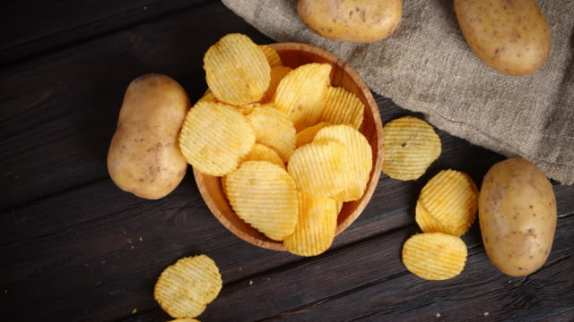 The chips on the plate slowly rotated. The chips on the plate slowly rotated. On wooden background potato chip stock videos & royalty-free footage