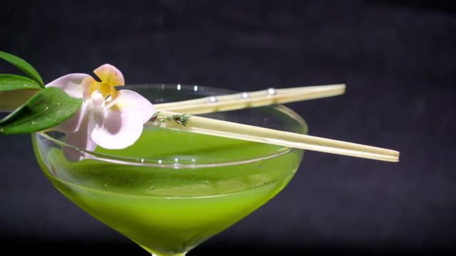 die stäbchen mit der blume auf der oberseite des glases - tropischer cocktail stock-videos und b-roll-filmmaterial