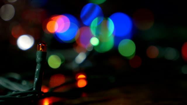 Die Weihnachtsgirlande blinkt mit farbigen Lichtern. Schöne unscharfe Hintergrund. – Video