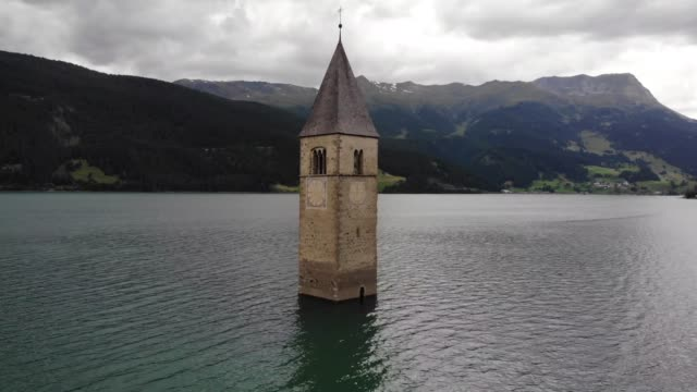 The church bell tower in the Lake Resia in Italy from drone 4k
