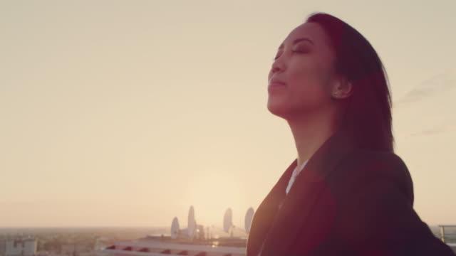 staden är min. asiatisk affärskvinna står på taket med öppna armar - femininitet bildbanksvideor och videomaterial från bakom kulisserna
