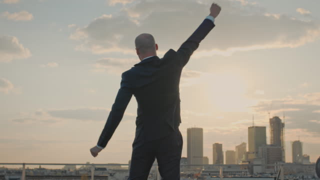 The city is mine. Businessman standing on roof with winning gesture