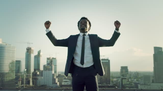 la città è mia. uomo d'affari in piedi sul tetto con gesto vincente - arto umano video stock e b–roll
