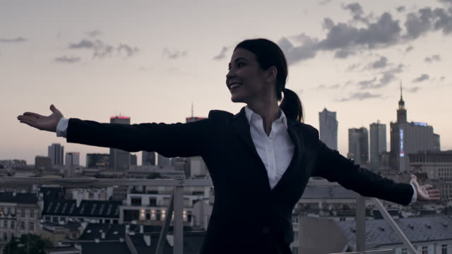 the city is mine. businesswoman standing on roof with open arms - femminilità video stock e b–roll