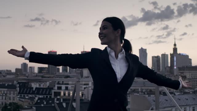 街は私のものだ開いている腕で屋根の上に立つビジネスウーマン - 身ぶり点の映像素材/bロール