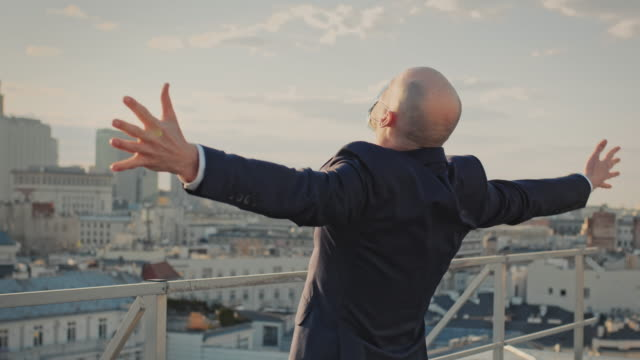 The city is mine. Businesswoman standing on roof with open arms
