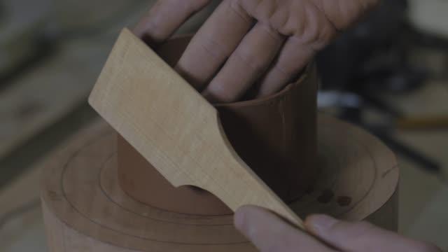 vídeos de stock, filmes e b-roll de o mestre da argila faz o molde para o bule de barro com uma espátula de madeira especial. bule de barro artesanal yixing para cerimônia do chá. bule de cerâmica roxa. vídeo 4k. 59,94 fps - cerâmica artesanato