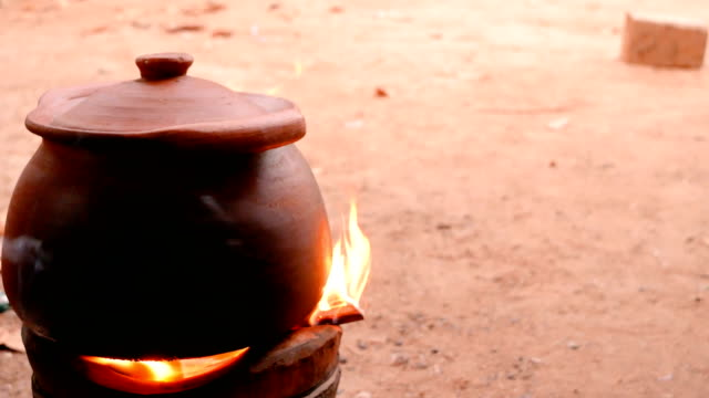 The clay pot is located on the fireplace with firewood and smoke. Traditional cooking methods.