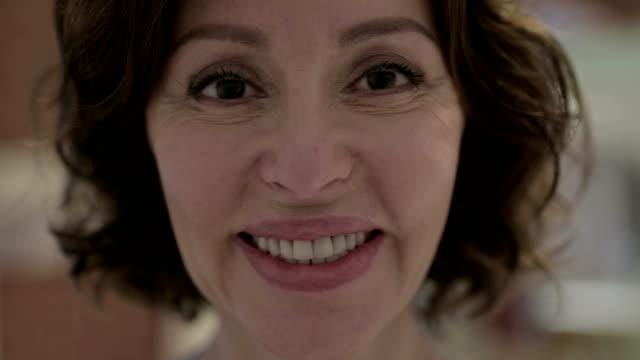 vidéos et rushes de le se béangle vers le haut de vieille femme gaie souriant à l'appareil-photo - une seule femme d'âge mûr