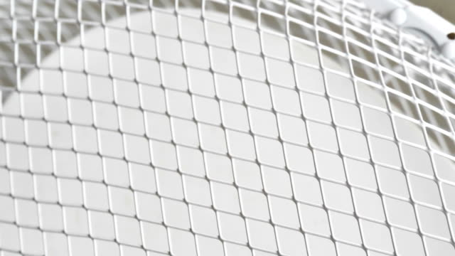 The closer look of the white netted cover of the electric fan