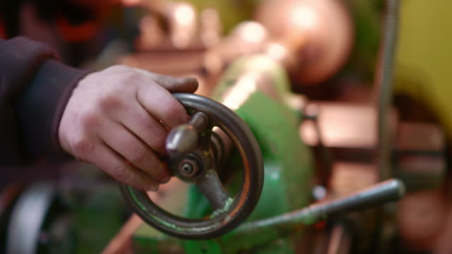 The close-up shot of the hands of the man working on the lathe