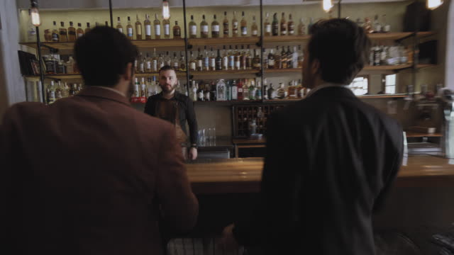 the colleagues arriving at the bar for a beer - bancone bar video stock e b–roll