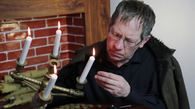 The collector looks at his wealth with lit candles. video