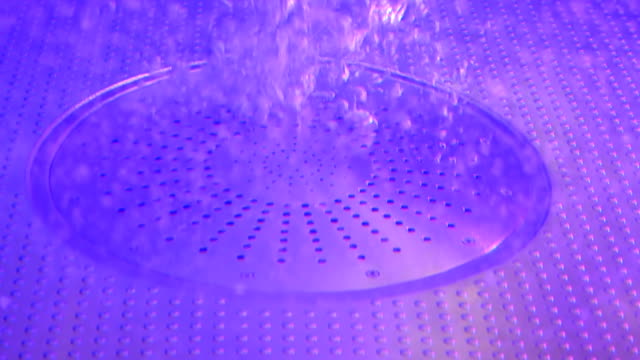 The colorfully illuminated water bubbling in the hot jacuzzi - vídeo