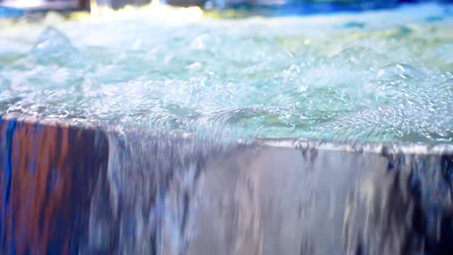The colorfully illuminated water bubbling in the hot tub poured over the edge - vídeo
