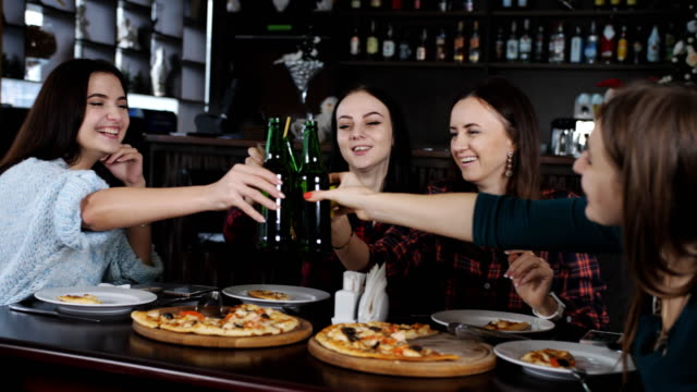 The company of beautiful girls in the pizzeria clinking bottles of beer. video
