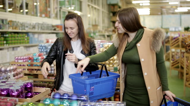 The company of cheerful friends in the supermarket to make purchases of Christmas decorations, getting ready for Christmas.
