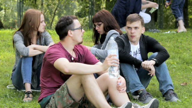 The company of friends on a picnic, guy drinking bottled water video