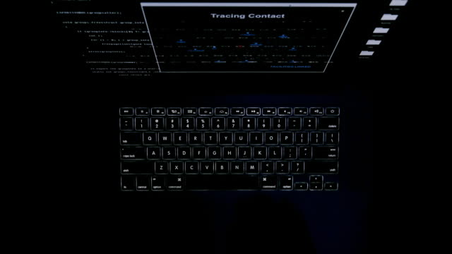 The computer keyboard glows in the dark. Keyboard backlight. The fingers are typing on the keyboard. The hacker works at night in total darkness. Computer monitor screen. Top view. video