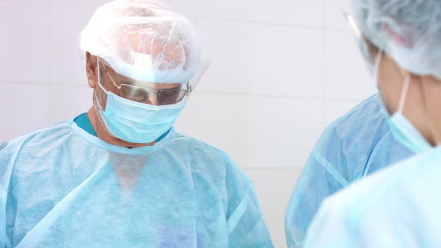 The concentrated surgeon performs the operation The concentrated surgeon performs the operation with medical team in surgery room implant stock videos & royalty-free footage