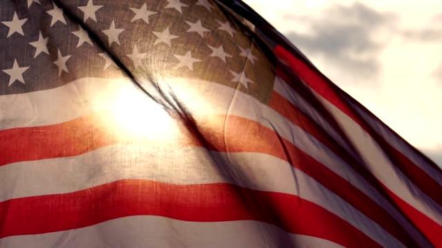 vidéos et rushes de le concept, fête du travail: drapeau des états-unis contre le ciel et la lumière du coucher du soleil - patriotisme