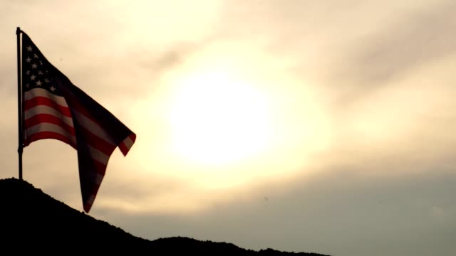 the concept, labor day: flag of the united states against the sky and light of the sunset - fourth of july стоковые видео и кадры b-roll