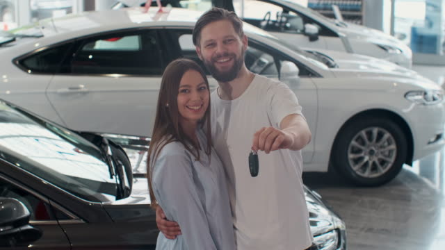 The concept of buying or renting a car. Young happy interracial couple with new car keys. The concept of buying or renting a car. Young happy interracial couple with new car keys car shopping stock videos & royalty-free footage